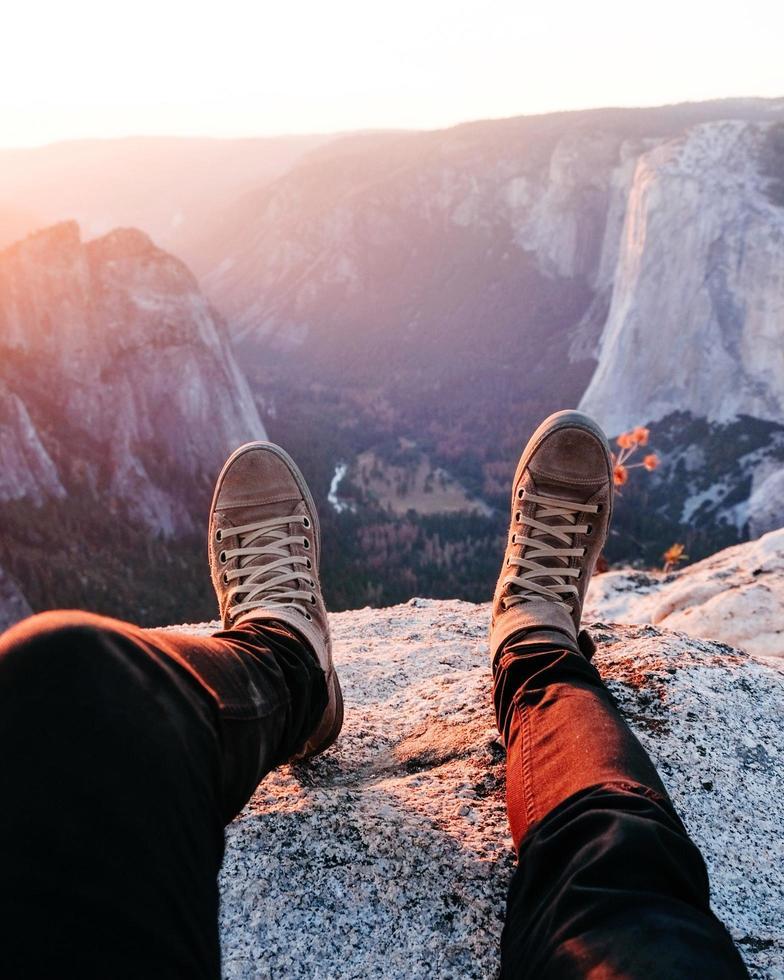 Person, die auf felsigem Berg während Sonnenaufgang sitzt foto