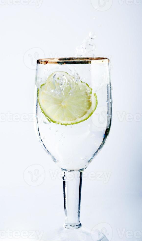 Kalk spritzt in ein Glas Wasser foto