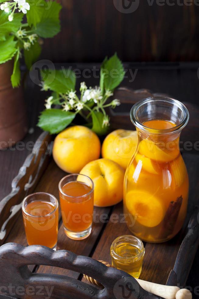 hausgemachter Schnaps aus Aprikosen und Zimt mit frischen Blumen foto
