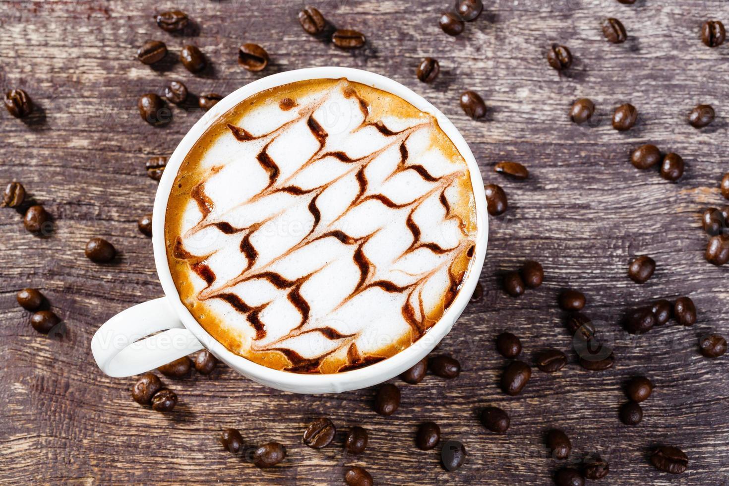 Tasse Kaffee und geröstete Bohne auf altem Holztisch foto