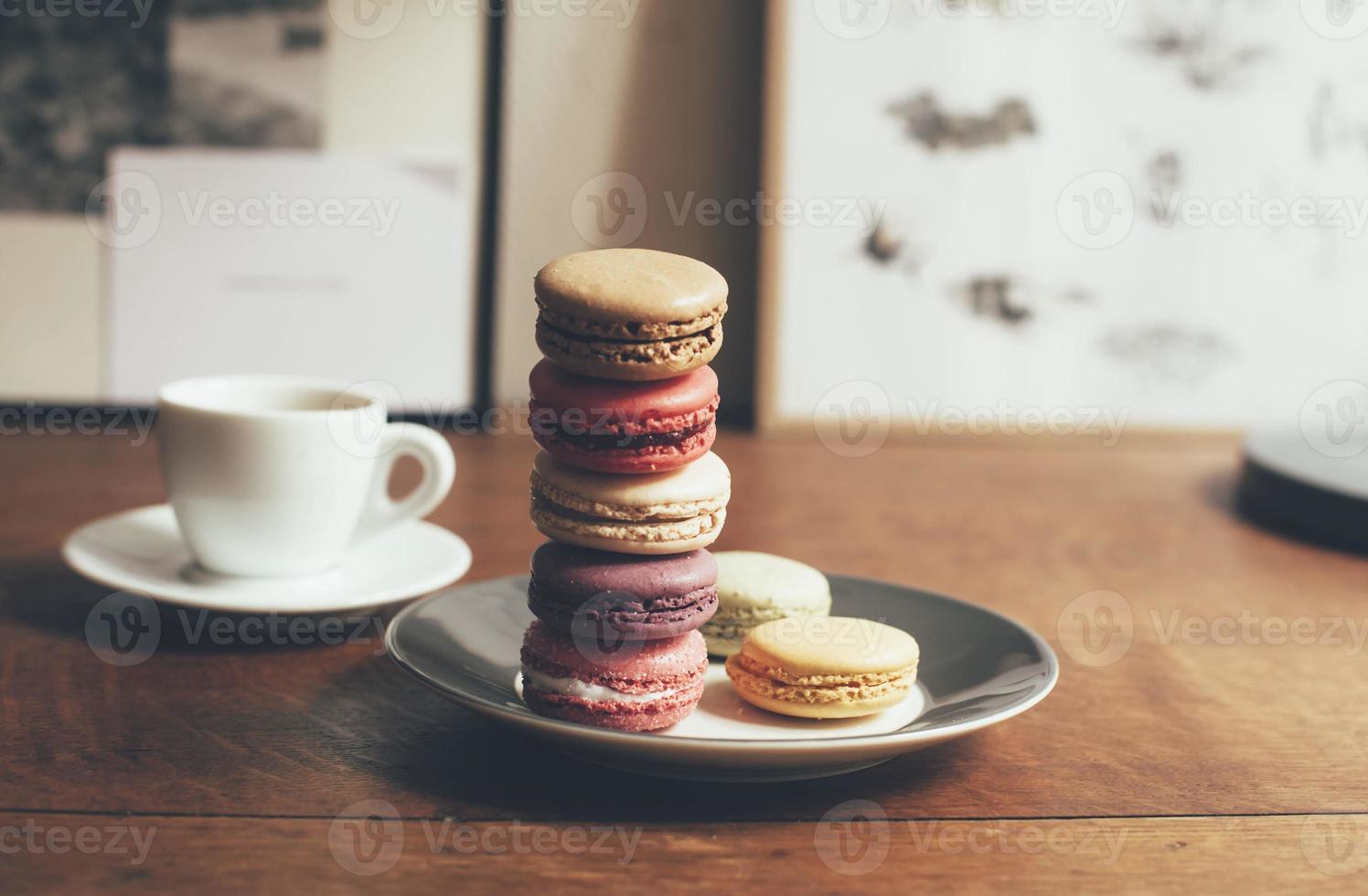 Kaffee und etwas Makronendessert auf dem Holztisch foto