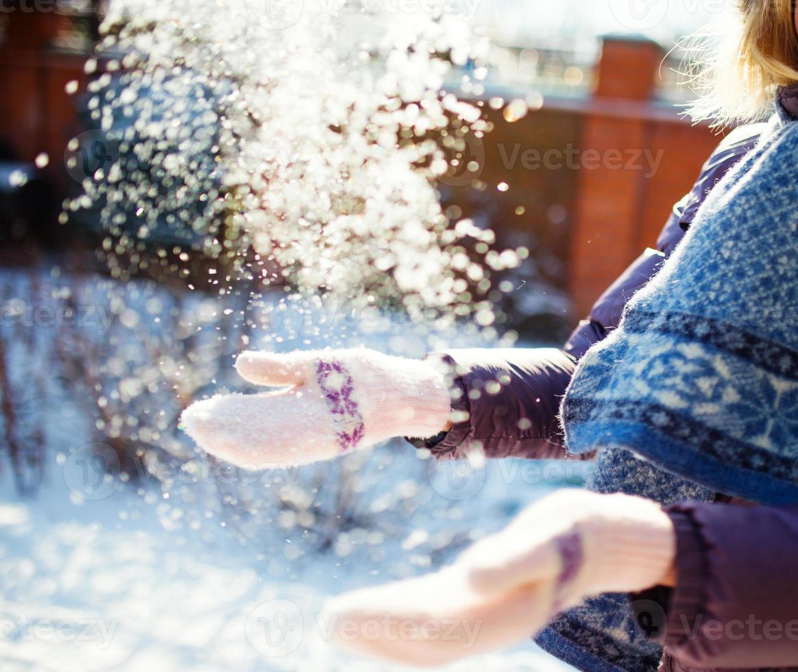 Frauen spielen mit Schnee am sonnigen Wintertag foto