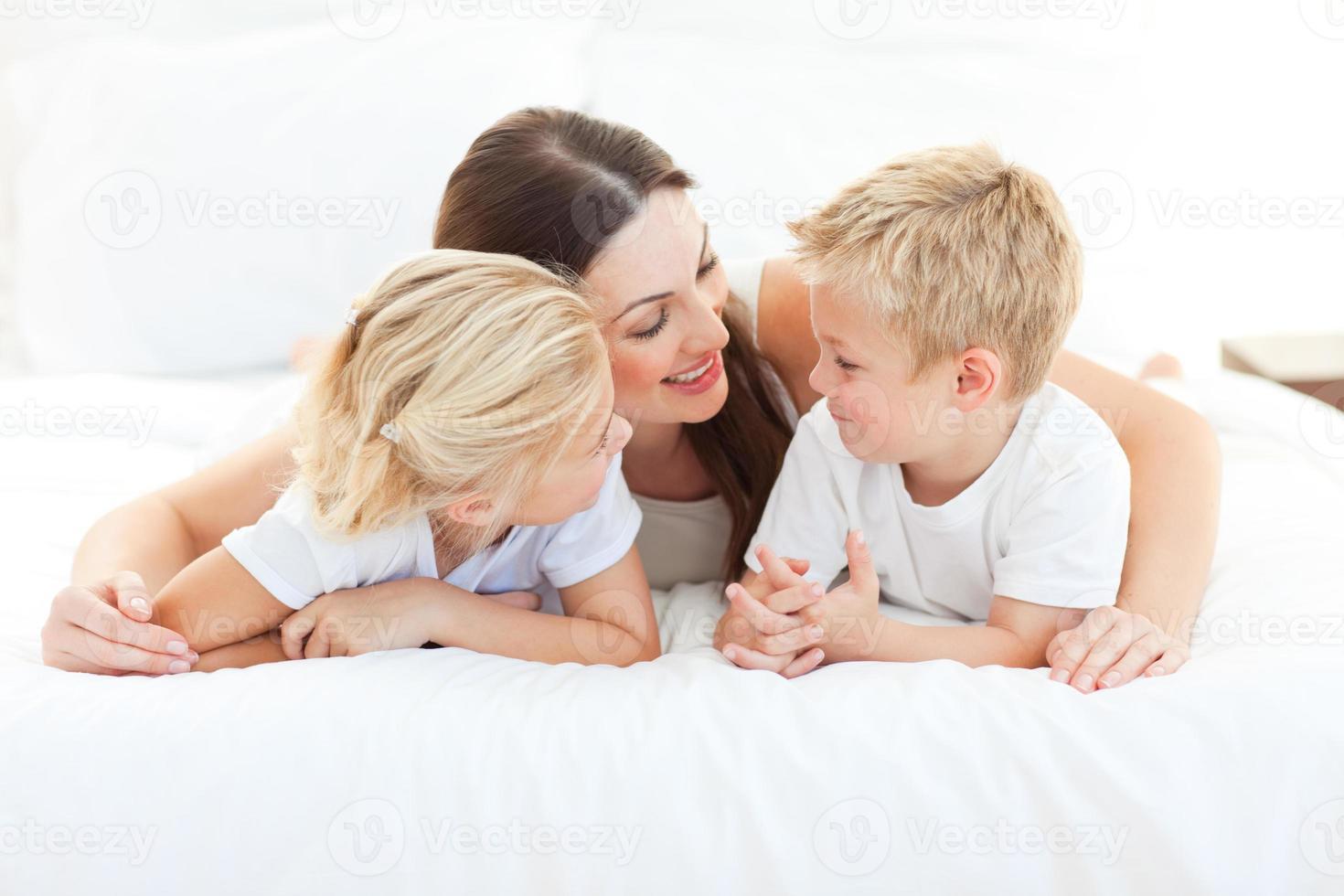 fröhliche Kinder und ihre Mutter diskutieren über das Liegen auf einem Bett foto