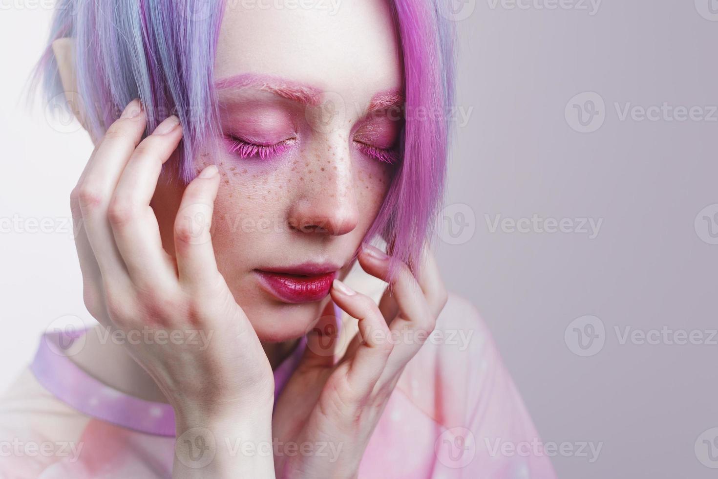 junges Mädchen mit rosa Augen und Haaren, wie eine Puppe foto