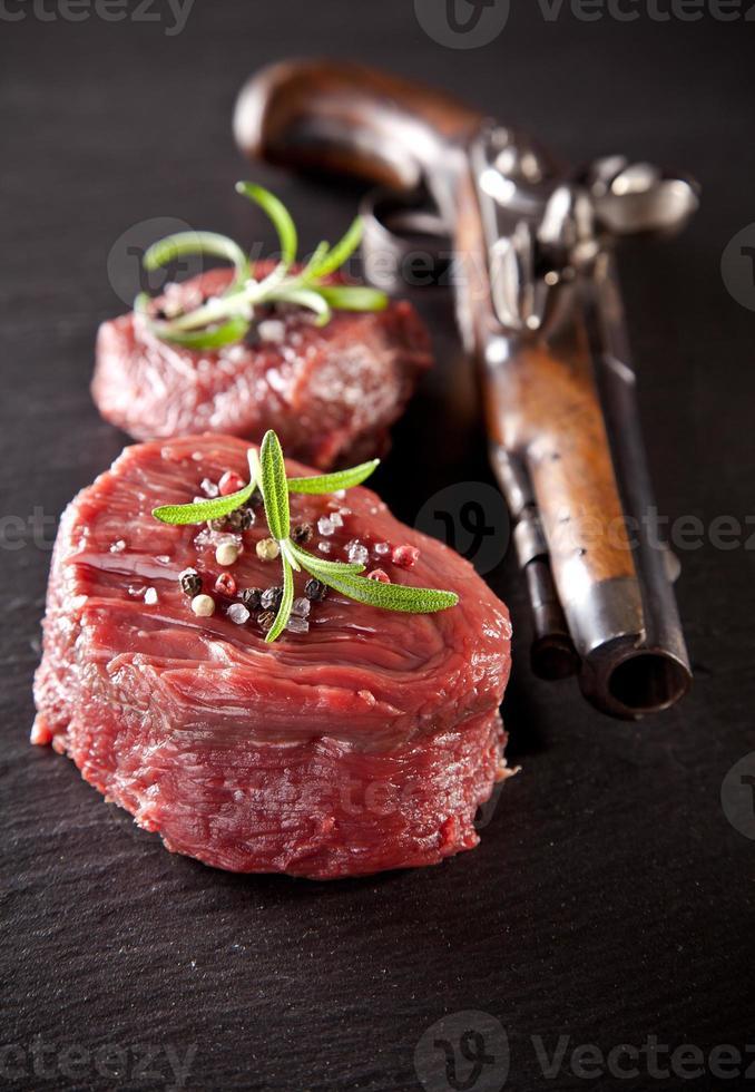 frisches rohes Rindersteak auf schwarzem Stein foto