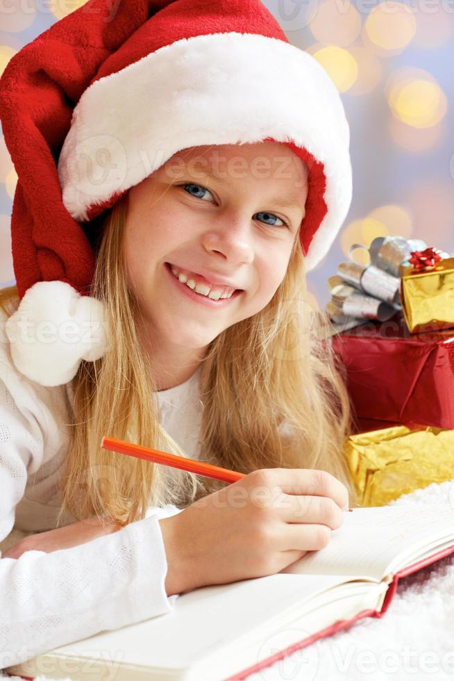 Porträt des kleinen niedlichen Mädchens mit Weihnachtsgeschenk. foto