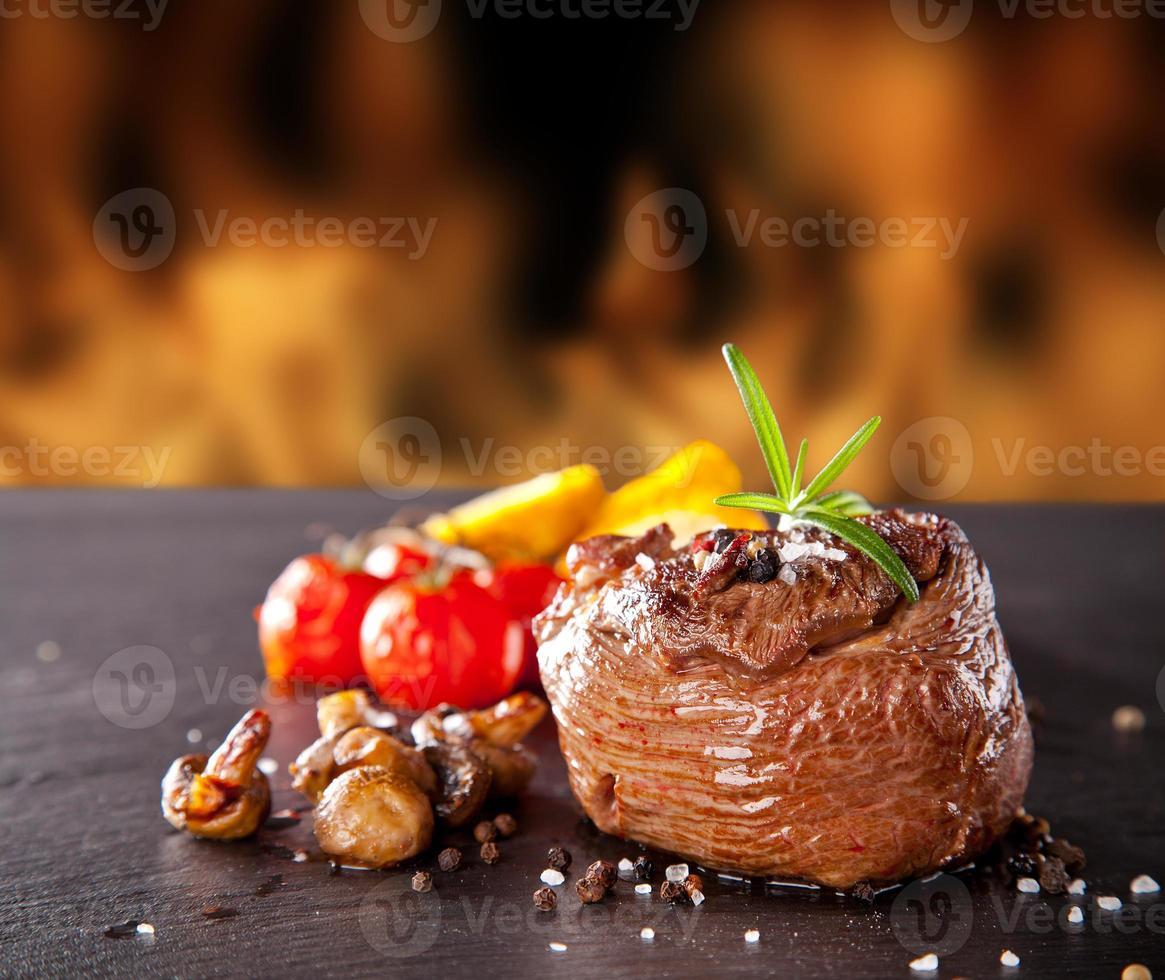 frisches Rindersteak auf schwarzem Stein und Feuer foto