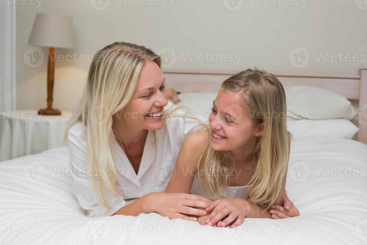 Frau, die Tochter beim Liegen im Bett ansieht foto