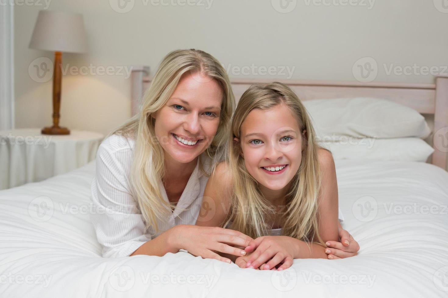 Frau mit Tochter im Bett zu Hause liegen foto