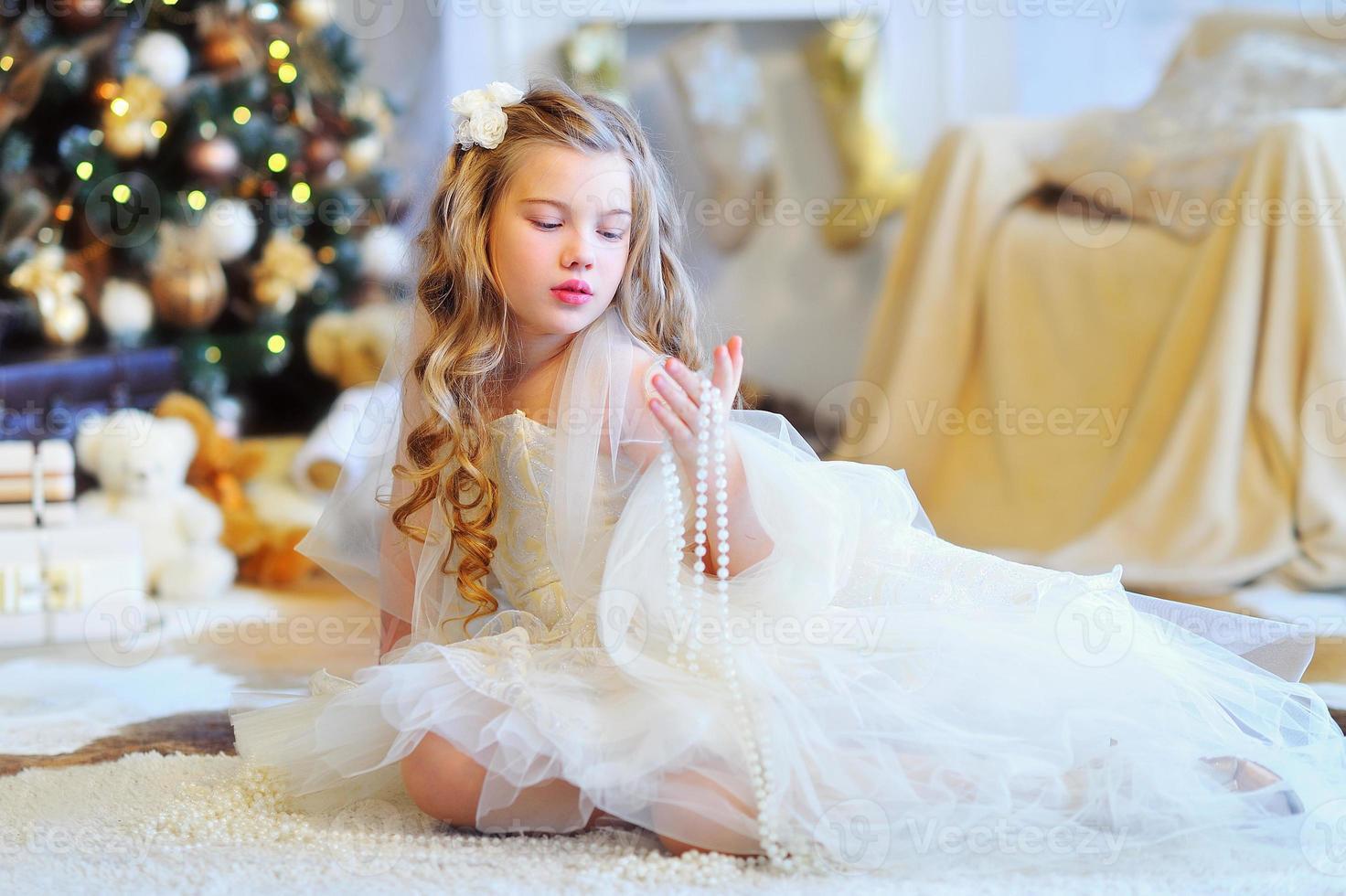 entzückendes Mädchen durch den Weihnachtsbaum foto