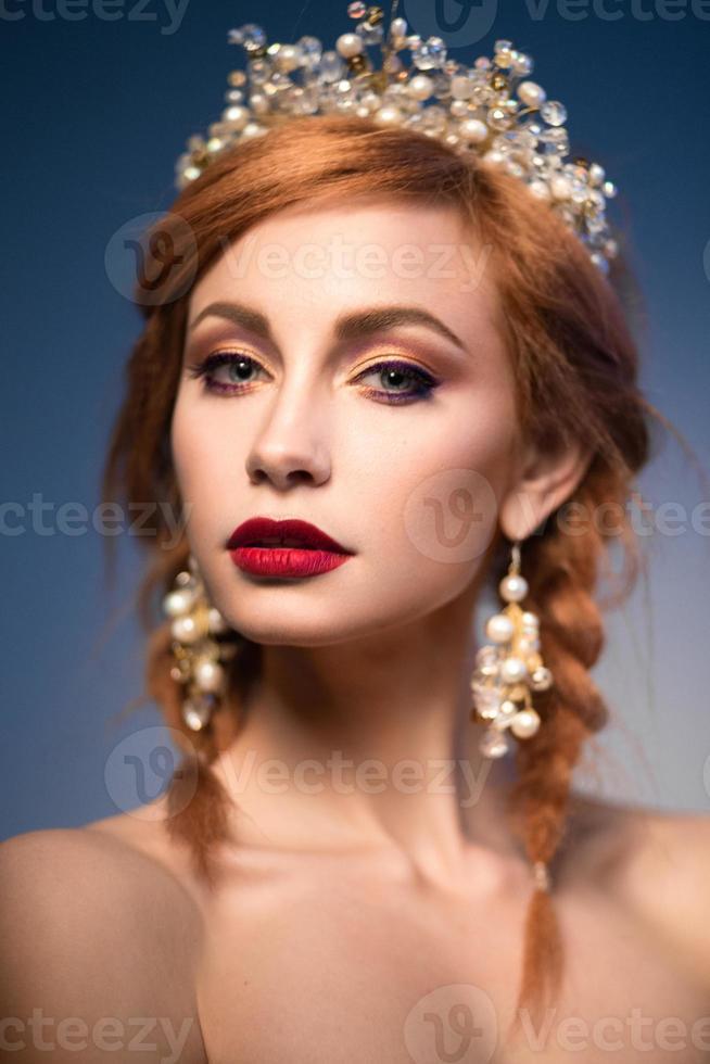 schöne Ingwerfrau mit Krone und roten Lippen foto