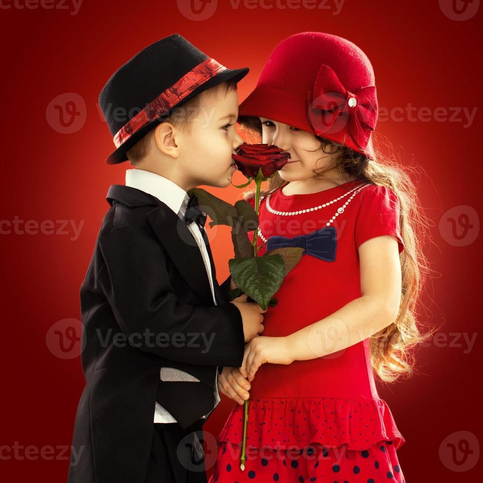 schöner kleiner Junge, der Mädchen eine Rose gibt foto