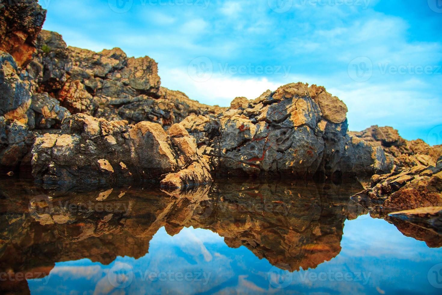 Felsen und ihr Spiegelbild im Meer tagsüber foto