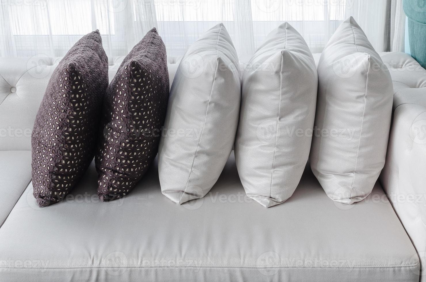 Reihe von Kissen auf weißem modernem Sofa im Wohnzimmer foto
