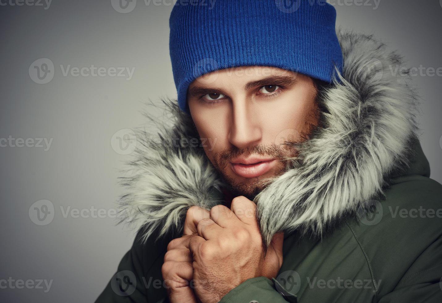 brutales Gesicht eines Mannes mit Bartborsten und Kapuzenwinter foto