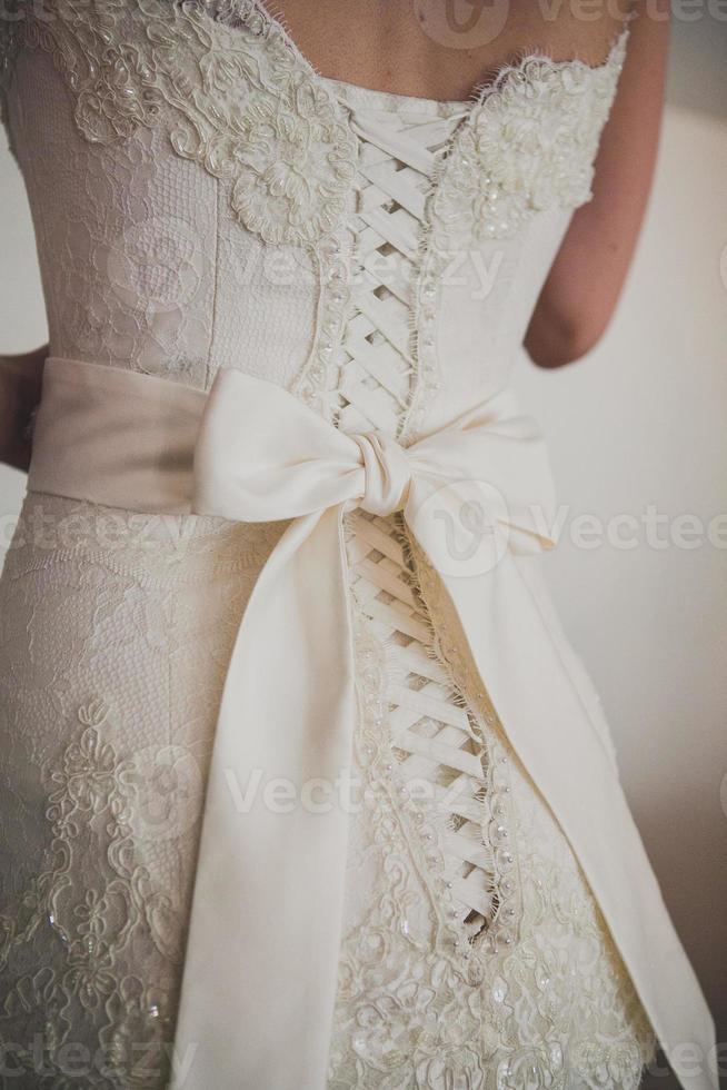 schönes luxuriöses Spitzenhochzeitskleid und weiße Schleife foto