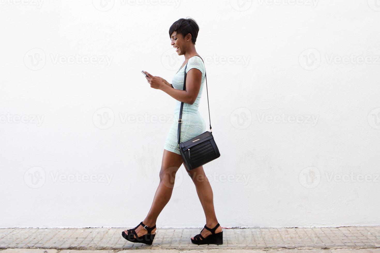 lächelnde junge Frau, die geht und Handy ansieht foto