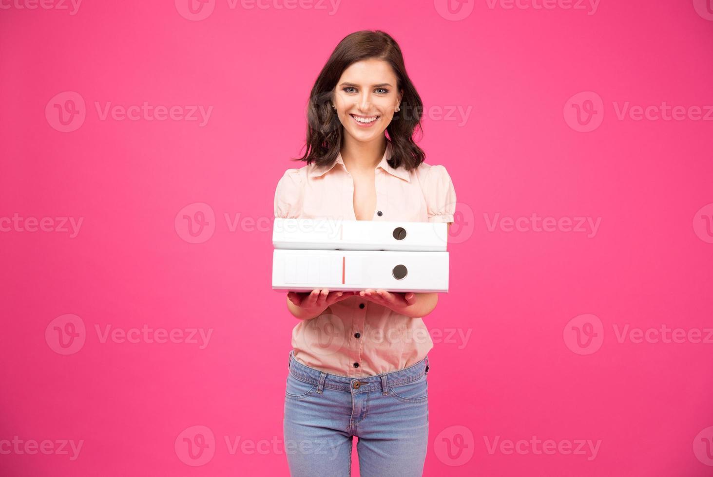 lächelnde junge Frau, die mit Ordnern steht foto