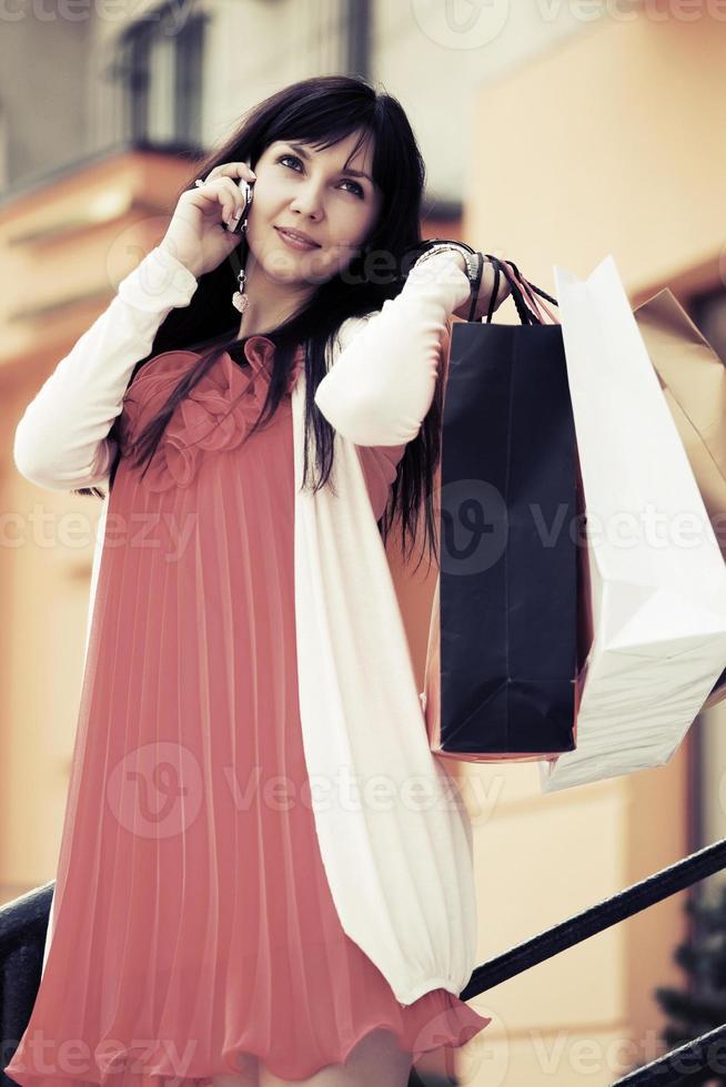 Modefrau mit Einkaufstaschen, die auf Handy anrufen foto