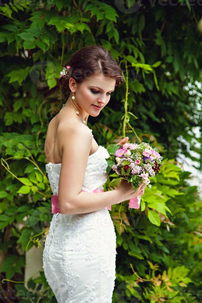 schöne Braut mit Blumenstrauß im Freien foto