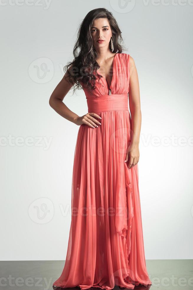 elegante Frau im roten Kleid, das mit Hand auf Hüfte steht foto