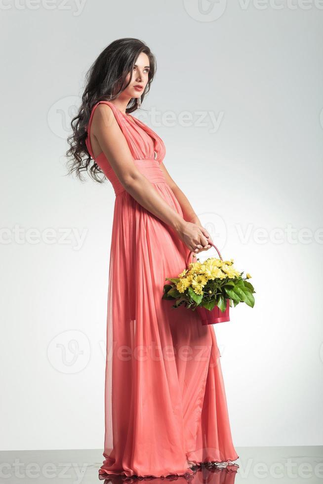 Modefrau im roten Kleid, das einen Blumenkorb hält foto
