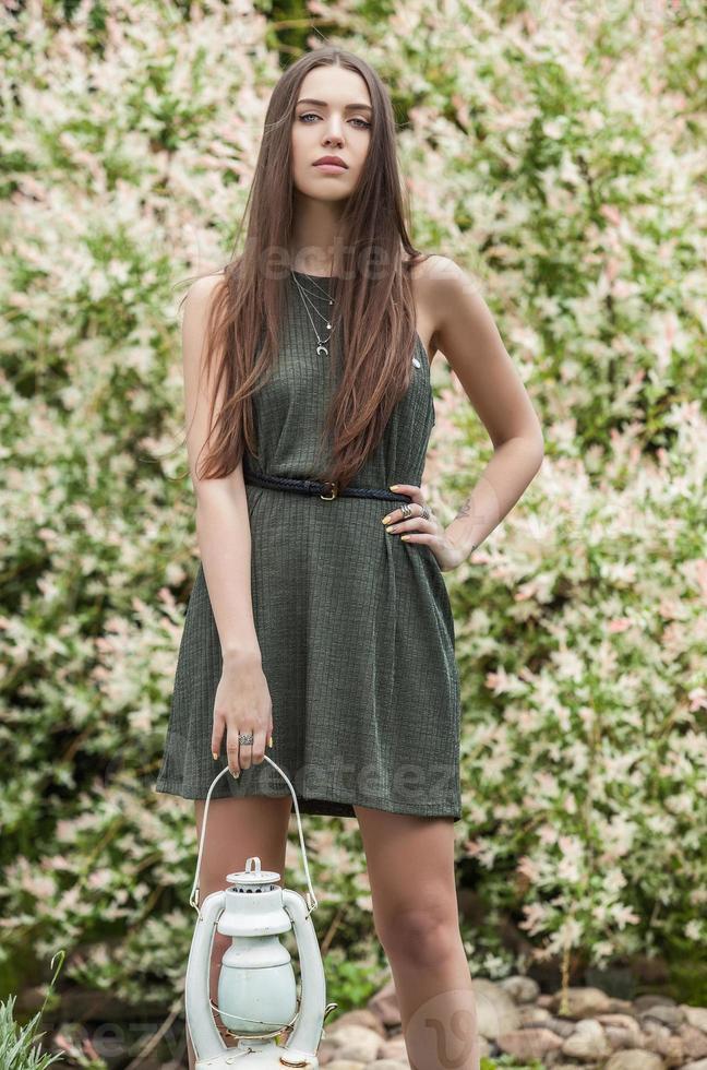 Frau im modischen grünen Kleid, das im Sommergarten aufwirft. foto