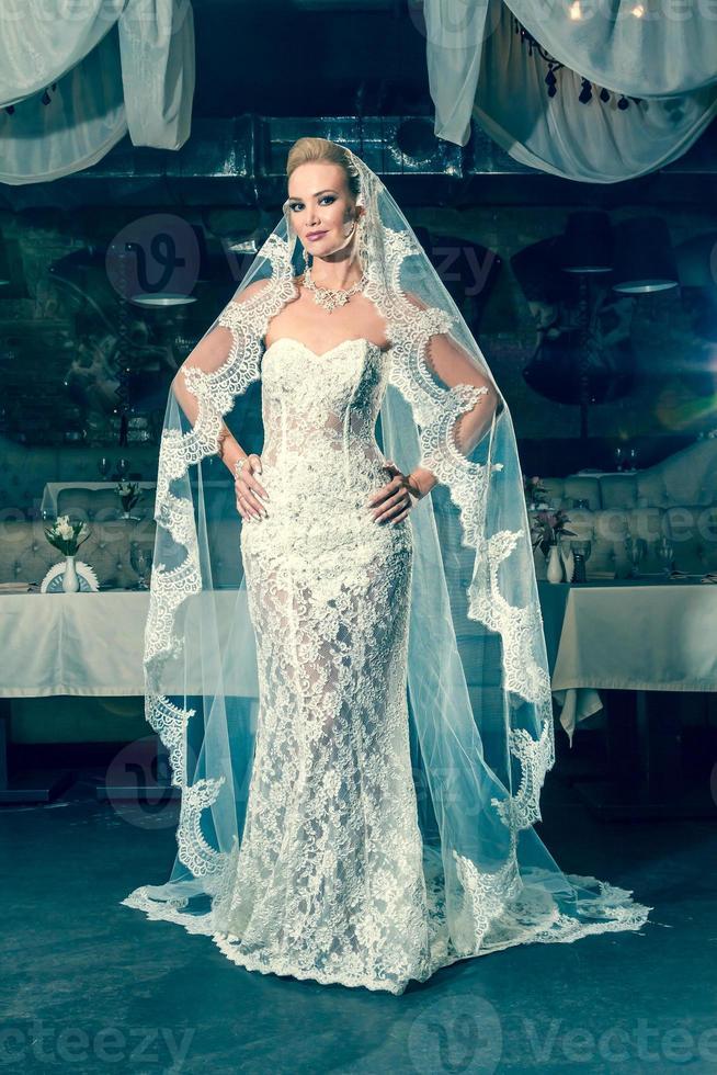 schöne Braut, die in der Mitte des Bankettsaals steht foto