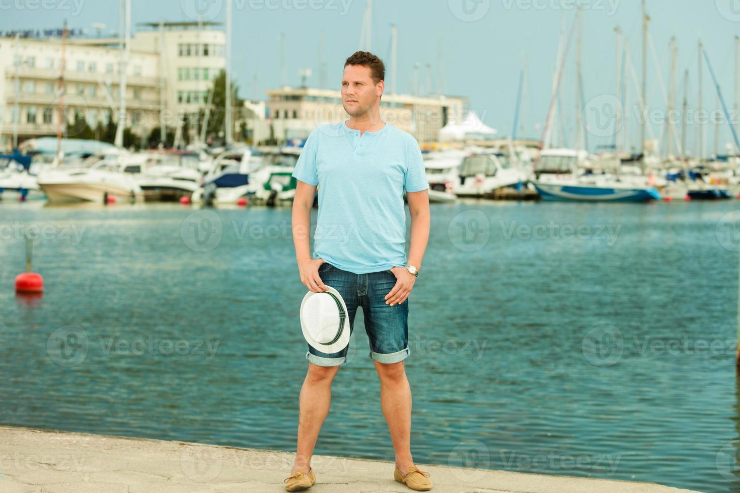 Modeporträt des gutaussehenden Mannes am Pier gegen Yachten foto
