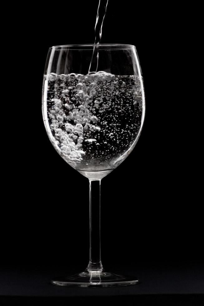 klares Weinglas mit Wasser foto