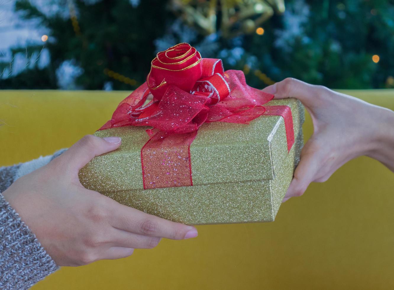 zwei Personen halten eine Geschenkbox foto