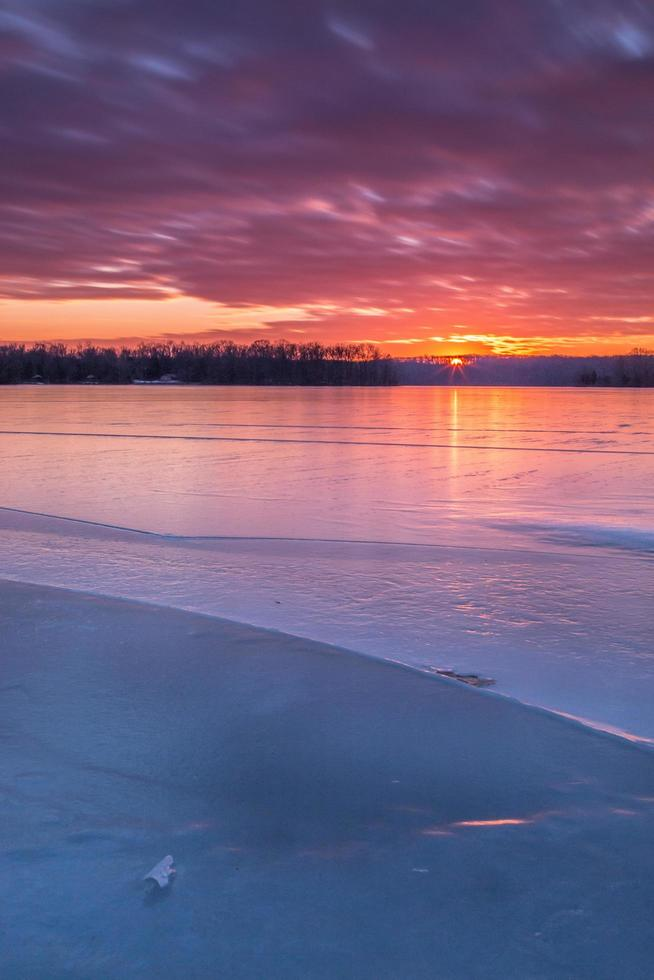 bunter Wintersonnenuntergang über einem zugefrorenen See foto