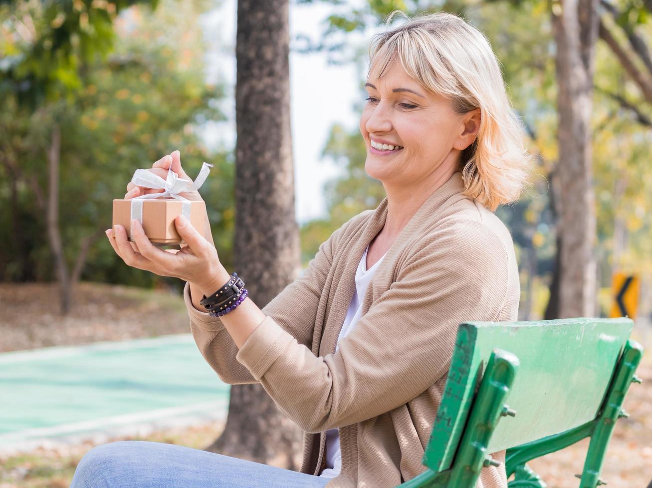 Frau, die Geschenk in einem Park öffnet foto