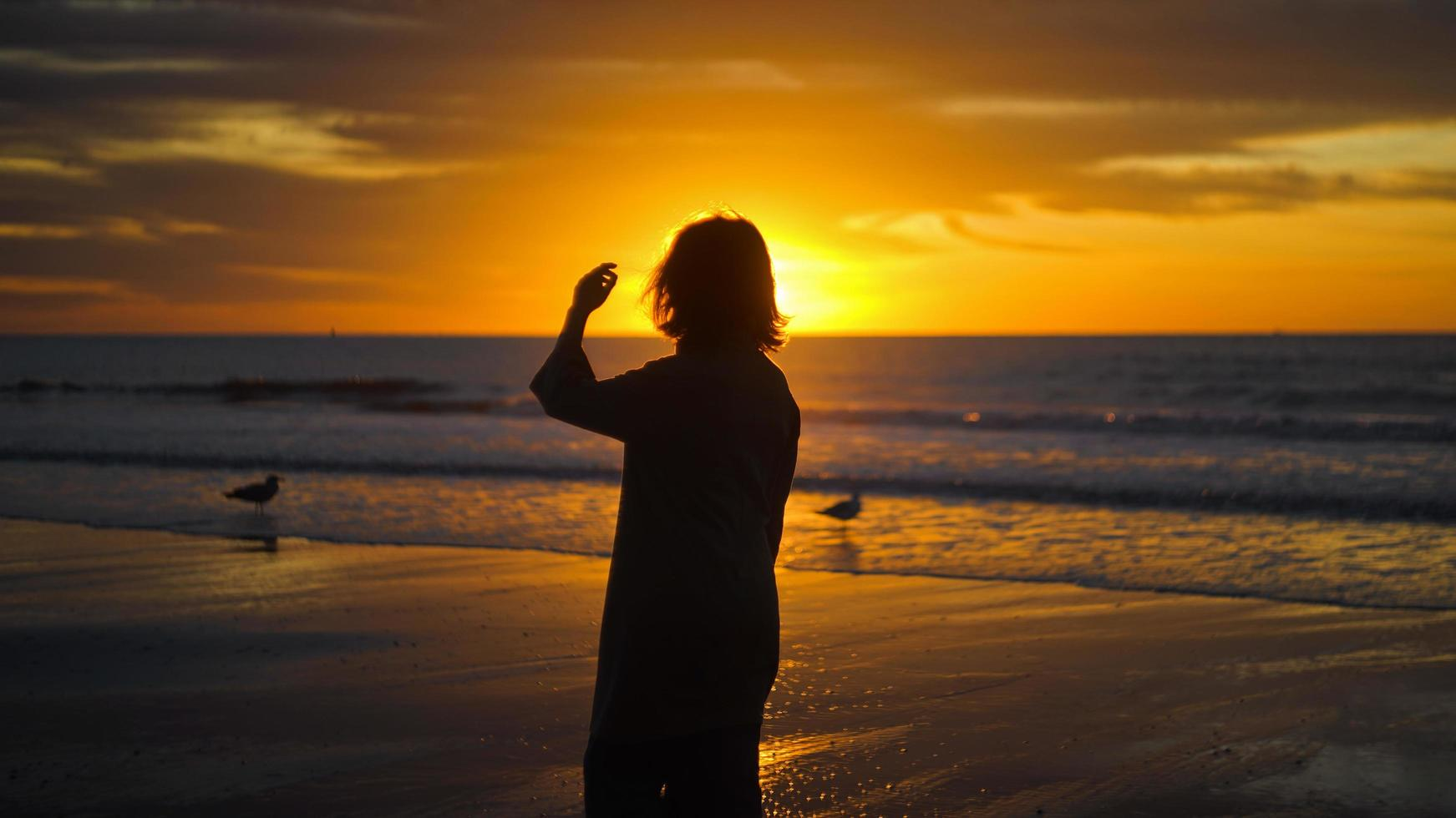 Silhouette der Frau, die an der Küste steht foto