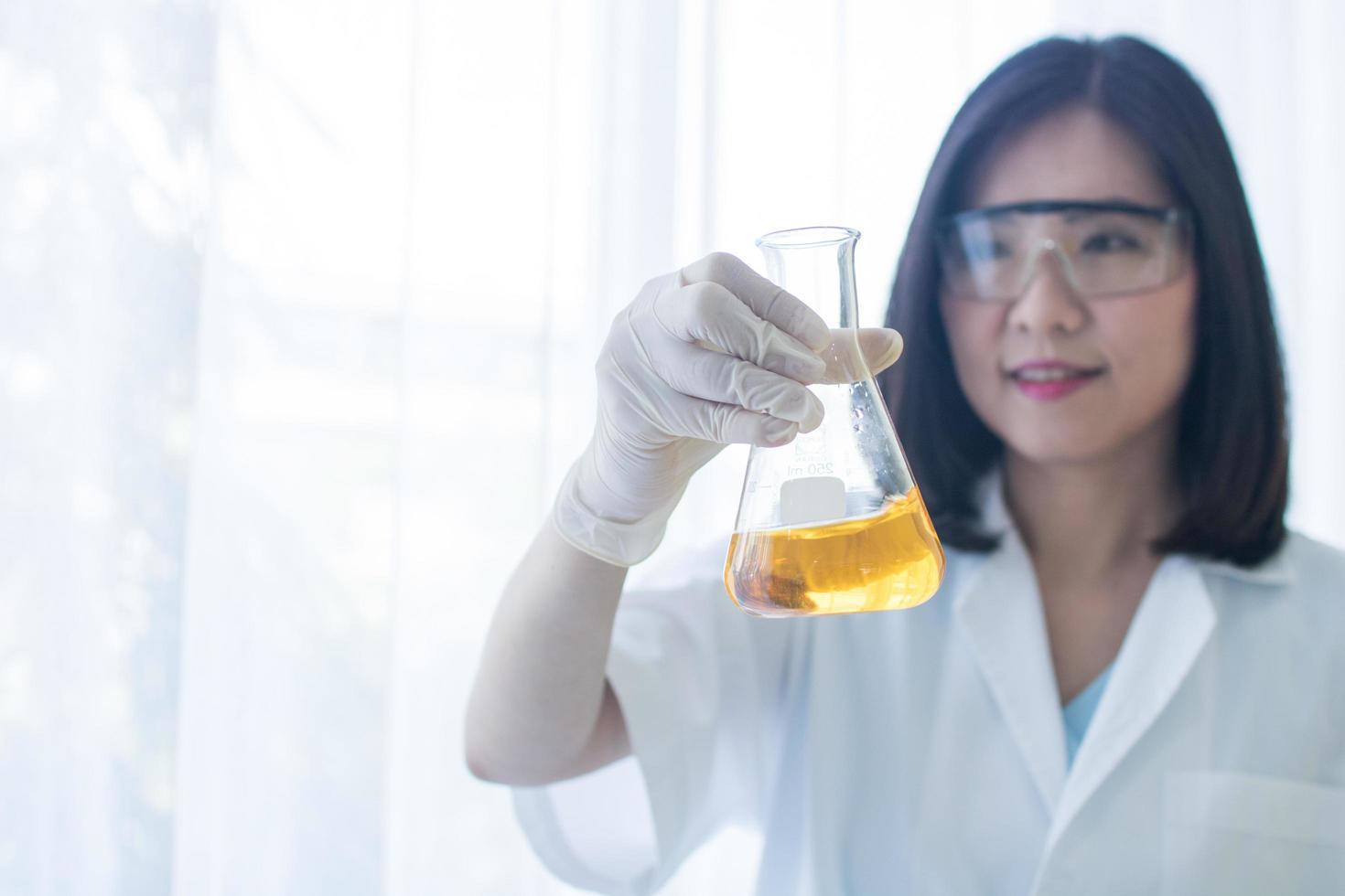 Frau, die Glaskolben im Labor hält foto