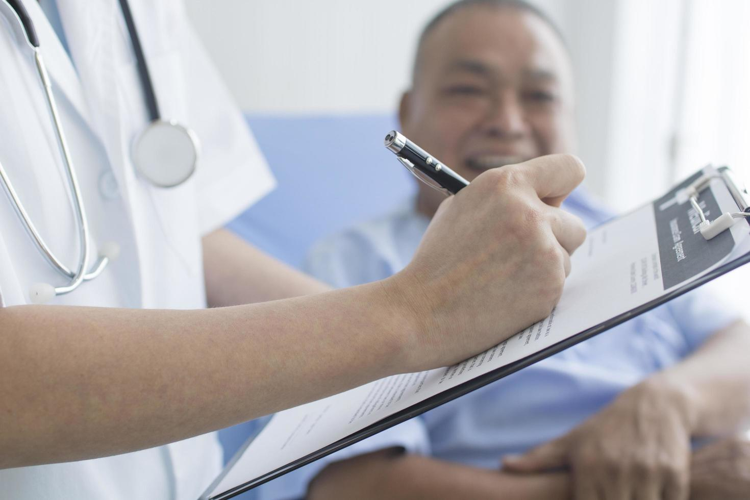 Arzt macht sich Notizen in der Zwischenablage für den Patienten foto