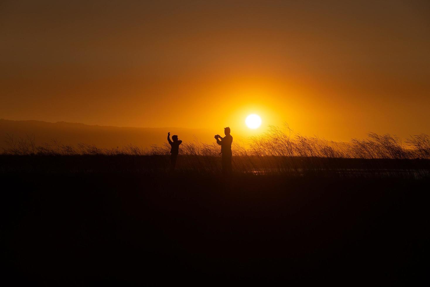 Vater und Sohn fotografieren im Sonnenuntergang foto
