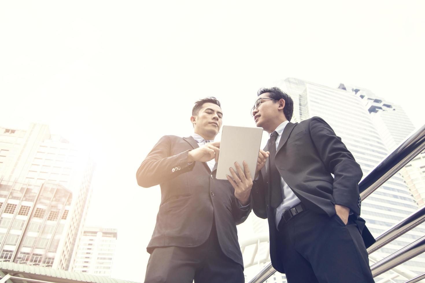 Zwei Geschäftsleute arbeiten draußen am Tablet foto