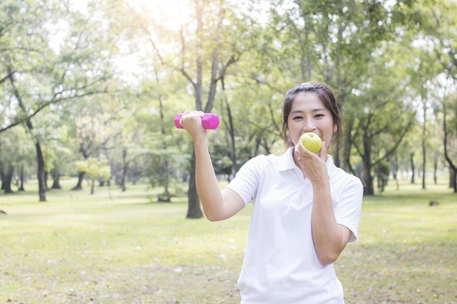 Frau, die einen Apfel ausübt und isst foto