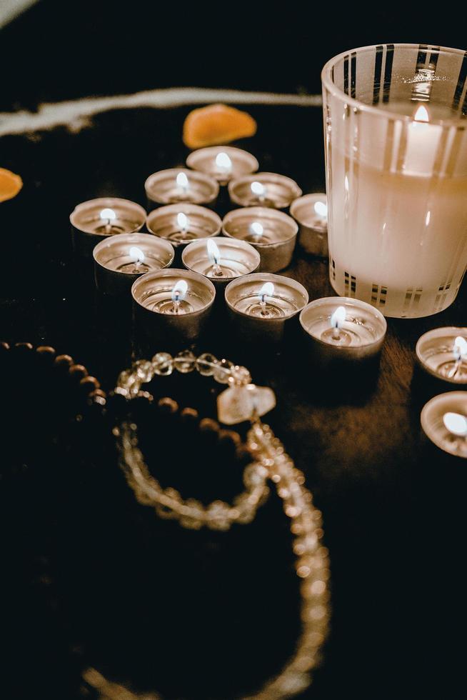 brennende Kerzen und Rosenkranz auf dem Tisch foto