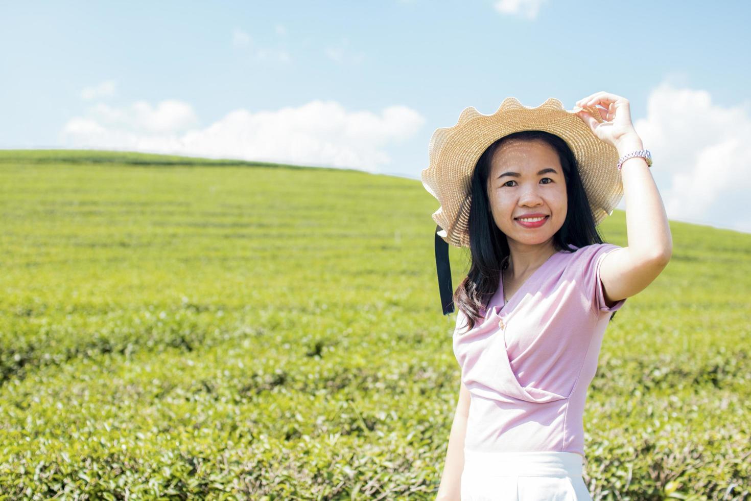 Frau, die Hut vor einem grünen Feld trägt foto