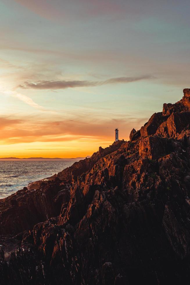 ein dramatischer Blick auf einen weißen Leuchtturm von den Felsen der Küste foto