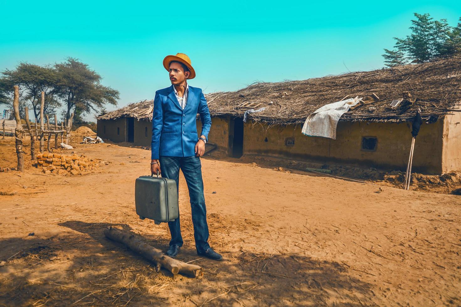 Mann mit Koffer neben Haus foto
