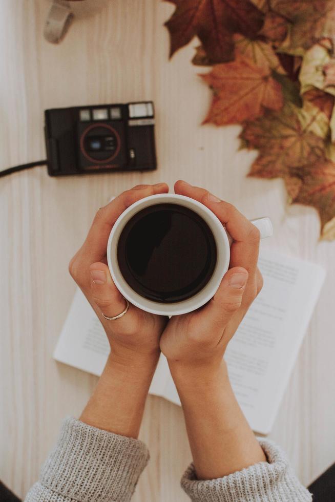 Person, die Kaffeetasse mit Kamera und Notizbuch auf Tisch hält foto