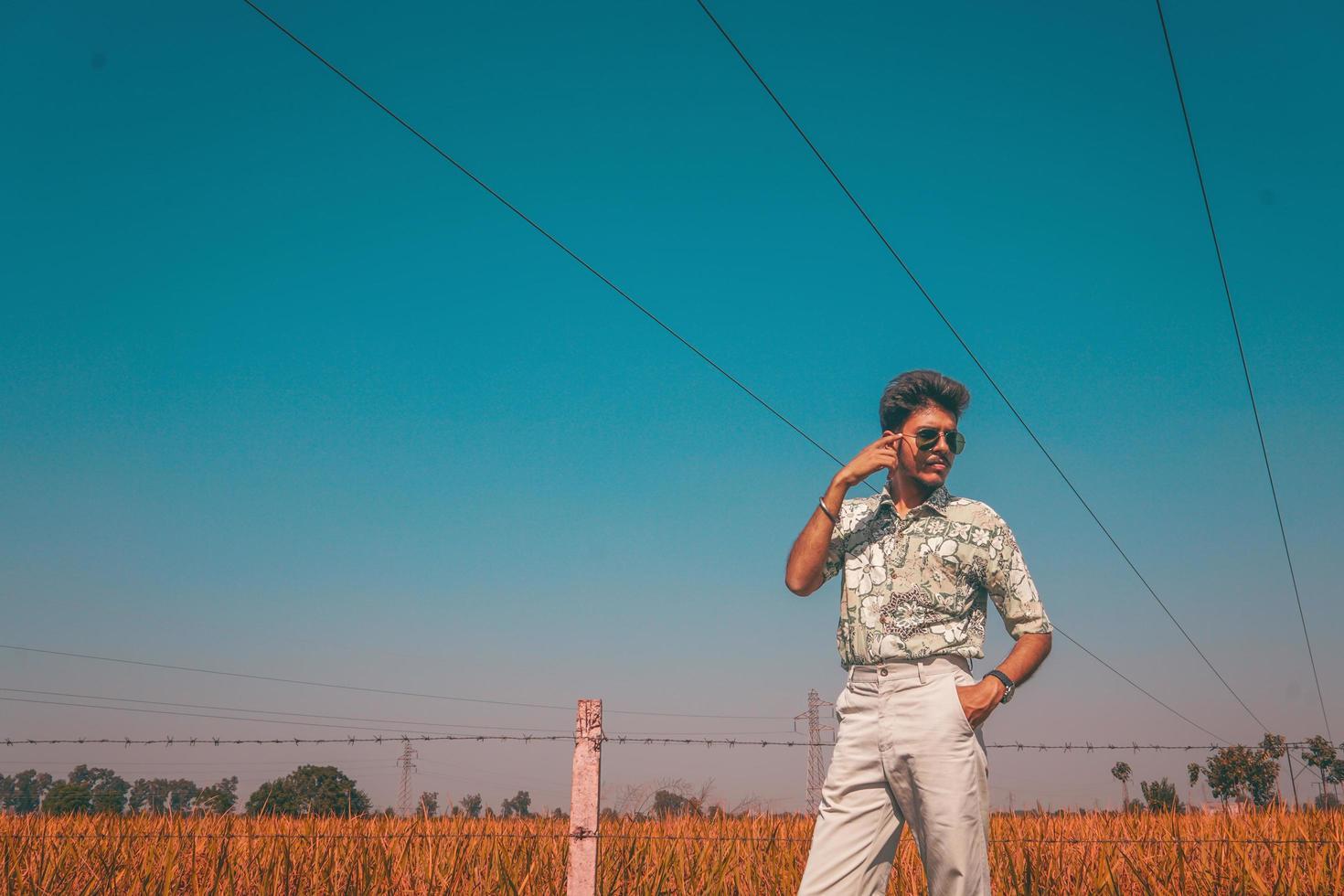 Mann in Sonnenbrille neben Zaun und Feld foto