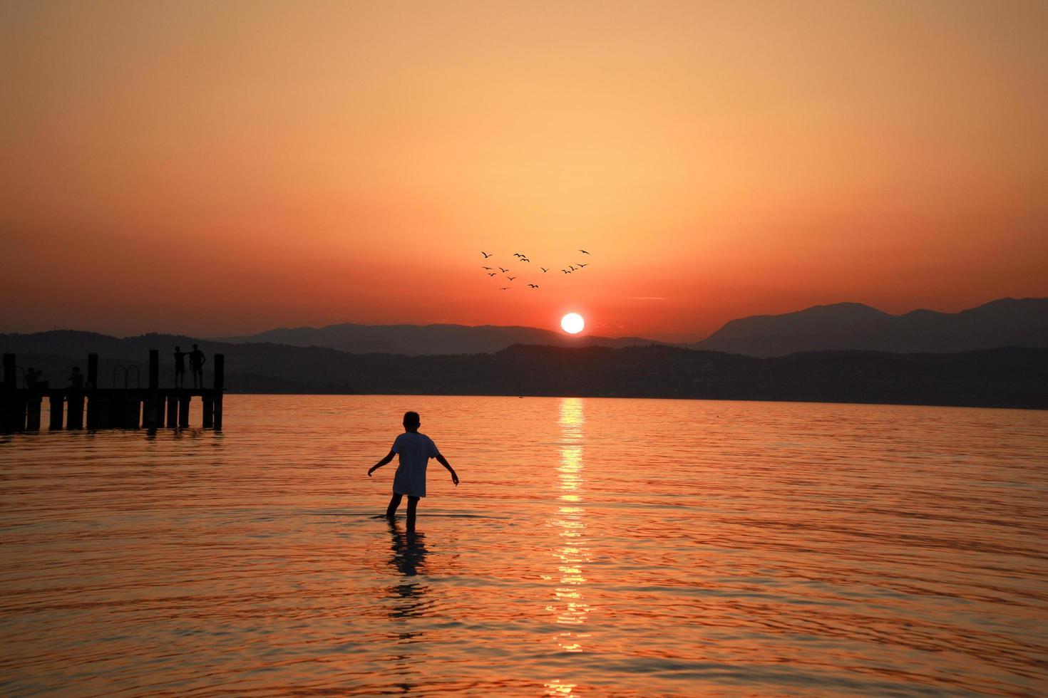 Mann, der im Meer unter goldener Stunde geht foto