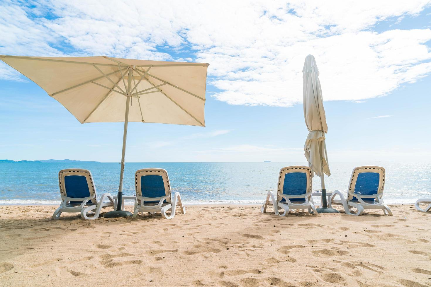 Outdoor mit Sonnenschirm und Stuhl am wunderschönen tropischen Strand und Meer foto