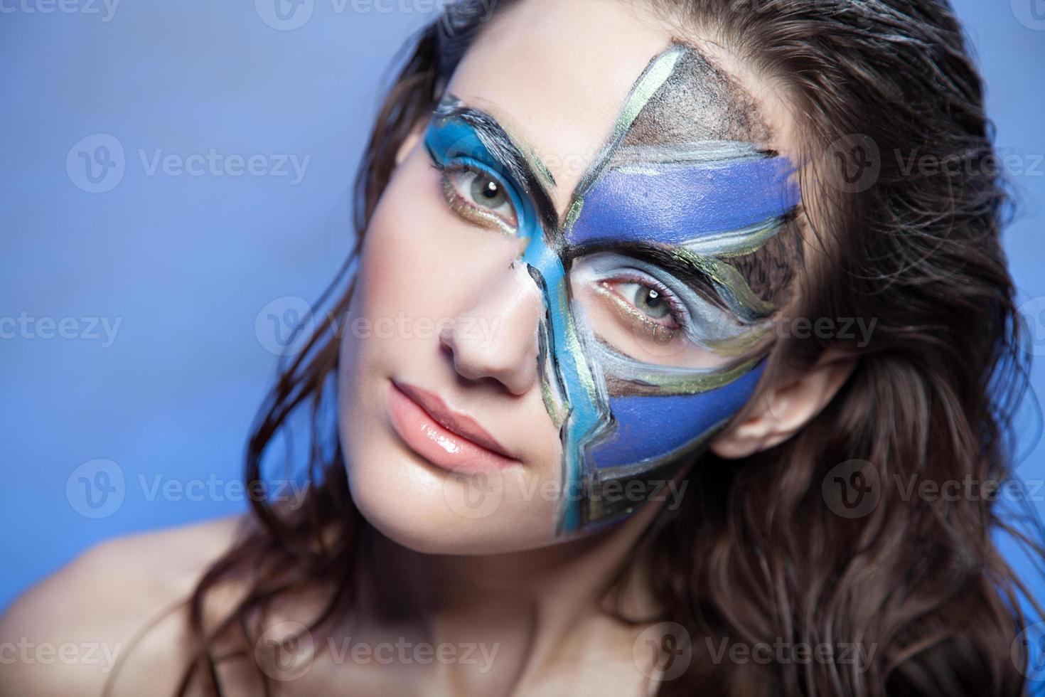 schönes Modefrauenfarbgesichtskunstporträt auf blauem Hintergrund foto
