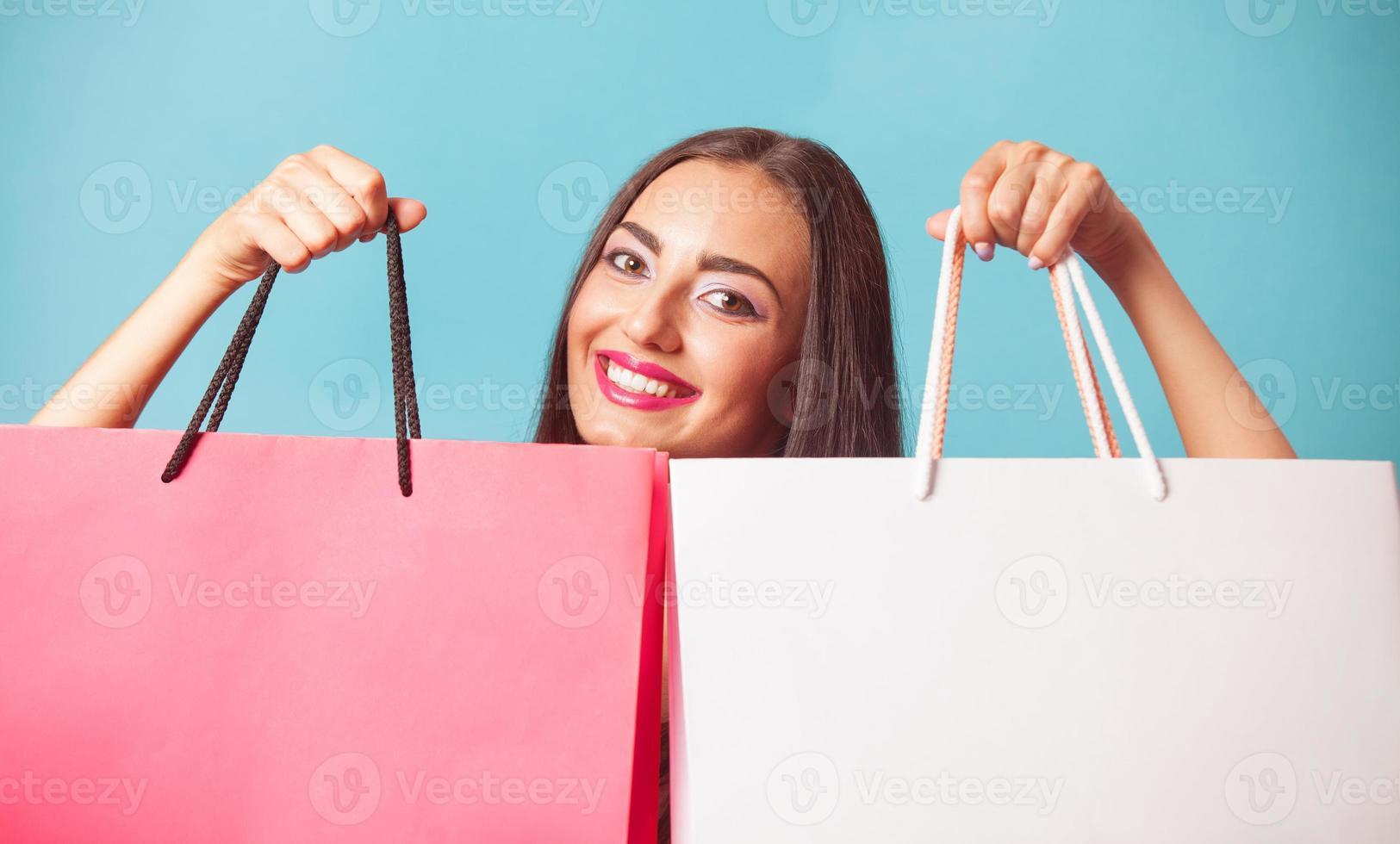 brünettes Mädchen mit Einkaufstüten auf blauem Backgorund. foto