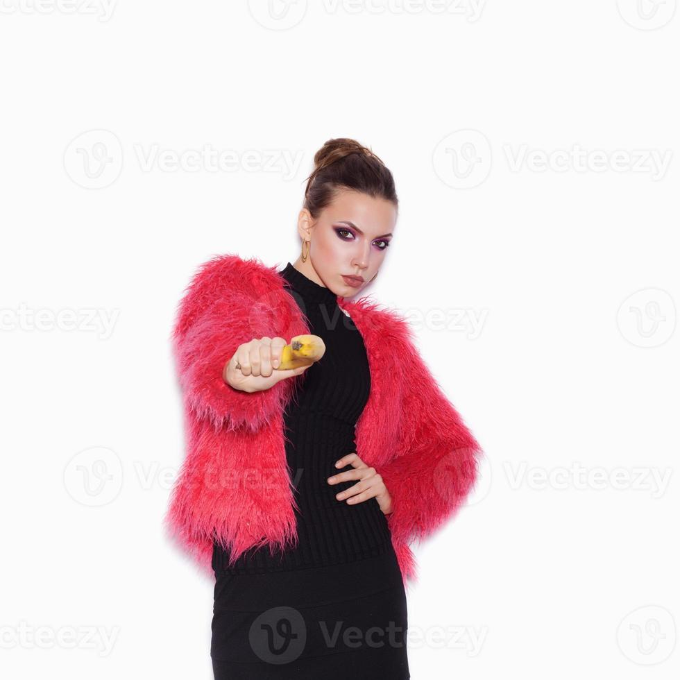 Frau, die rosa Pelzmantel trägt, der Spaß mit Banane macht foto
